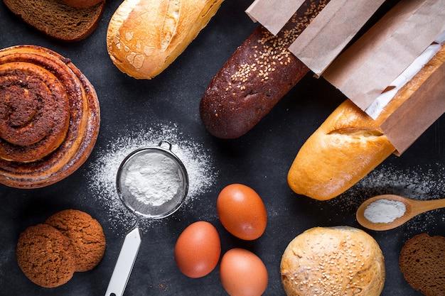 Пекарские ингредиенты для мучных и ржаных хлебобулочных изделий. свежий свежий хлеб, багет в бумажном пакете и булочки Premium Фотографии