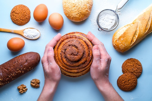 新鮮な自家製シナモンロールを保持しているパン屋。さまざまな新鮮で鮮明なベーカリー製品とベーキング成分 Premium写真