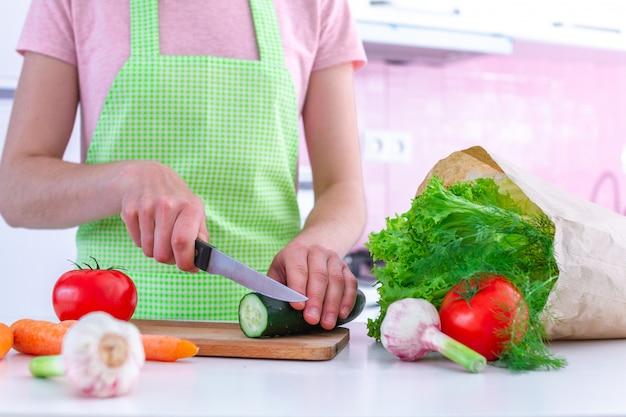 キッチンで野菜料理やサラダを調理するためのまな板の上の新鮮な有機キュウリを刻んでエプロンの女性。 Premium写真