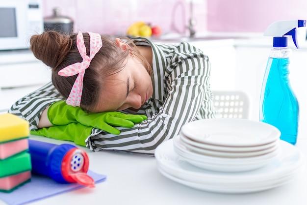 Усталая, перегруженная работой домохозяйка уснула и упала на стол из-за усталости от уборки дома из-за весенней уборки и тяжелой домашней работы Premium Фотографии