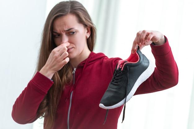女性は長いスポーツトレーニングとアクティブなライフスタイルの後、汗をかいたランニングシューズから不快な臭いを感じています。靴はクリーニングと臭気除去に必要です。靴の手入れと輝き Premium写真