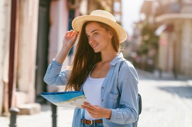 Путешественник женщина в шляпе, поиск правильного направления на карте путешествия во время путешествия по европе. отпуск и путешествия образ жизни Premium Фотографии