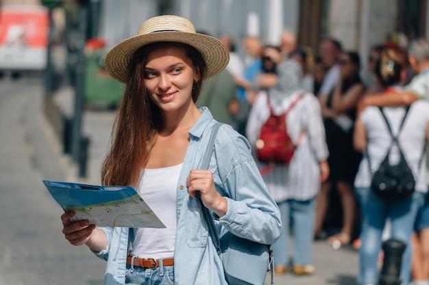 Женщина путешественника в шляпе ища правильное направление на карте перемещения среди толпы туристов пока путешествующ по европе. отпуск и путешествия образ жизни Premium Фотографии