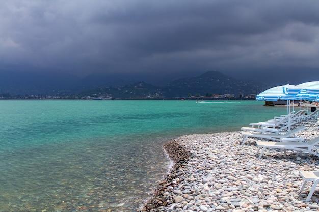 Бирюзовое море и галечный пляж с зонтиками и шезлонгами на фоне гор. отдых на море Premium Фотографии
