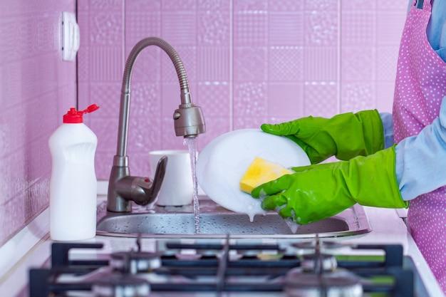 ゴム手袋とエプロンの主婦が自宅でスポンジと洗剤で皿を洗う Premium写真