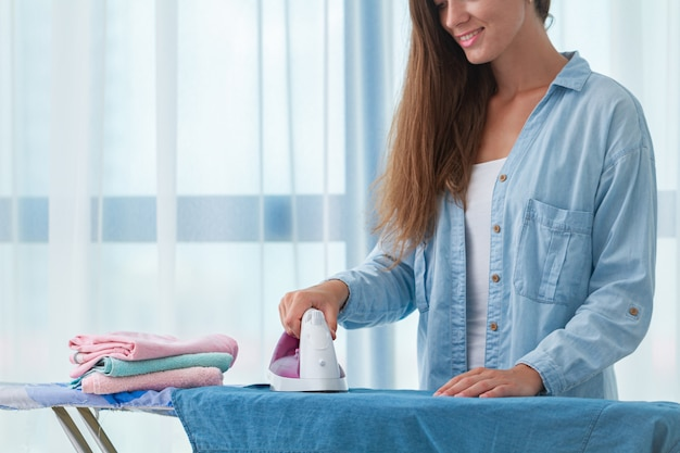 Молодая счастливая домохозяйка гладит после стирки на гладильной доске Premium Фотографии