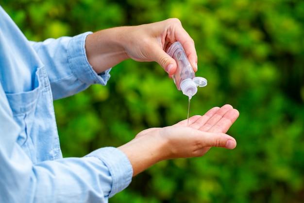 手の消毒のために公園で抗菌防腐剤ハンドジェルを適用する Premium写真