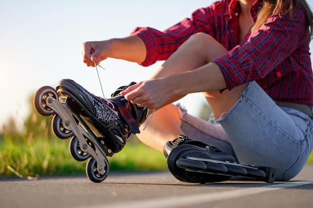 女性はインラインスケートのローラースケートをひもで締めます。屋外のティーンエイジャーのローラーブレード。 Premium写真