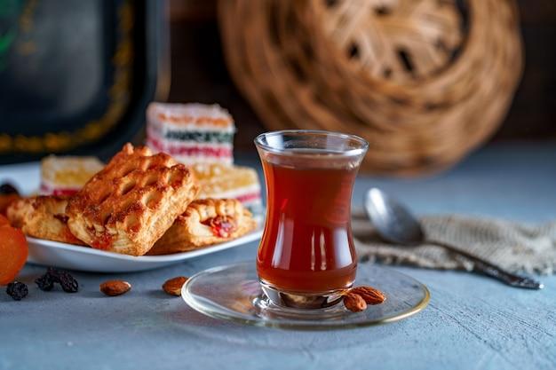 お菓子、ドライフルーツ、ナッツを使った伝統的なガラスのトルコ式ティー Premium写真