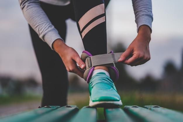 アスレチック女性は、屋外トレーニング中に歩くためのスポーツの重みをつけます。健康的でスポーツライフスタイル。 Premium写真