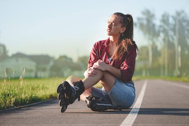 ローラーブレードとインラインスケート中に落ちた後あざを持っている女性の膝を負傷 Premium写真