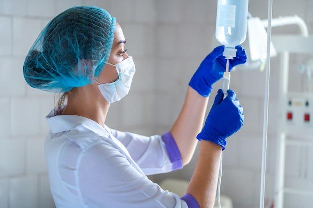 Медсестра готовит пациенту капельницу для процедуры в больнице Premium Фотографии