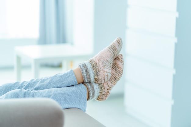 パジャマと居心地の良い柔らかい快適な冬の靴下を自宅でソファで休む女性 Premium写真