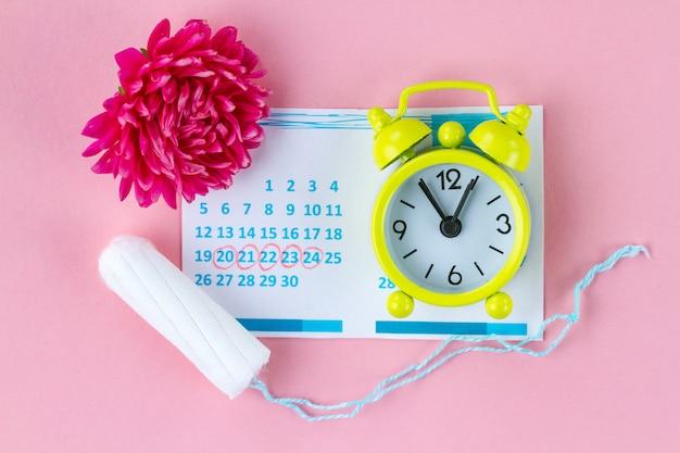 Тампоны для менструации, будильник, женский календарь и розовый цветок. гигиенический уход в критические дни. регулярный менструальный цикл. Premium Фотографии