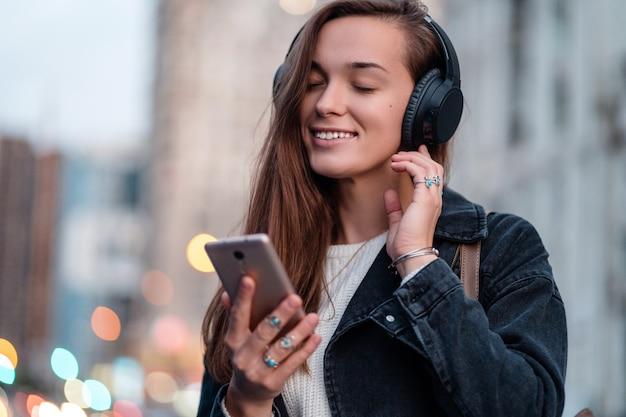 Подросток наслаждается и слушает музыку в черных беспроводных наушниках во время прогулки по городу Premium Фотографии