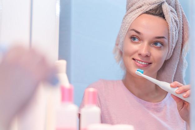 幸せな健康な女性は自宅の浴室で超音波電動歯ブラシを使用して歯を磨く Premium写真