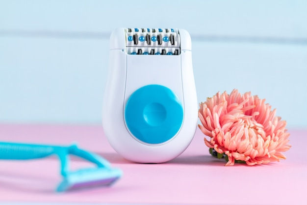 脱毛器、女性用シェービングカミソリ、ピンクの花。脱毛。不要な毛の除去。 Premium写真