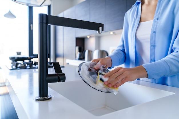 家事中の女性の食器洗浄 Premium写真