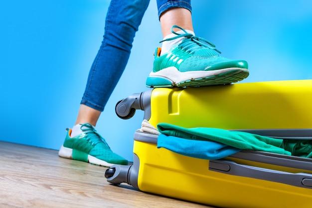 黄色のスーツケースに服を梱包します。旅行や出張に必要なものを梱包してください。休暇、休日。旅行のコンセプト Premium写真