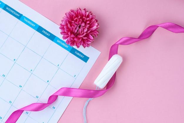 Регулярный менструальный цикл. тампоны, женский календарь, цветы. гигиенический уход в критические дни. женское и гинекологическое здравоохранение. Premium Фотографии