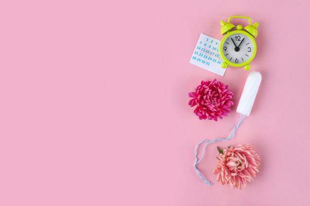 月経用タンポン、目覚まし時計、女性用カレンダー、ピンクの花。重要な日の衛生管理。定期的な月経周期。 Premium写真