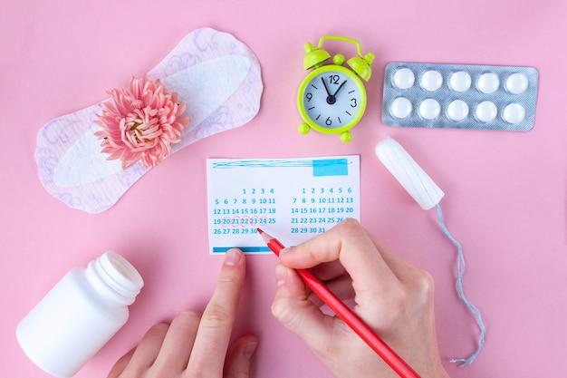 タンポン、フェミニン、クリティカルデイ用生理用ナプキン、フェミニンカレンダー、目覚まし時計、月経中の鎮痛剤、ピンクの花。月経中の衛生管理 Premium写真