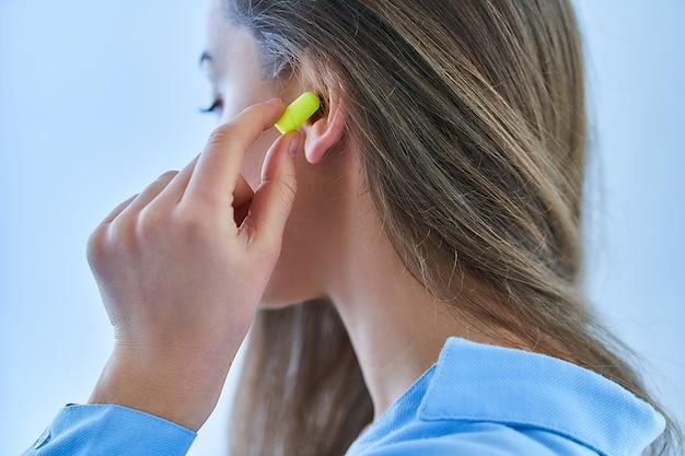 Молодая брюнетка женщина, используя затычки для ушей для защиты от шума Premium Фотографии