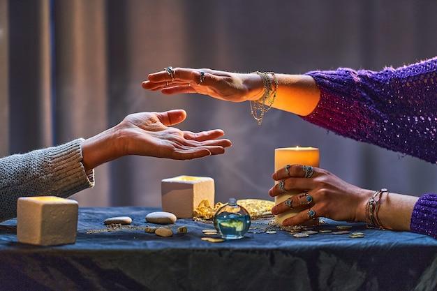 手相占いやキャンドルやその他の魔法のアクセサリーの周りの占いの儀式中にジプシー魔女の女性。魔法のイラスト Premium写真