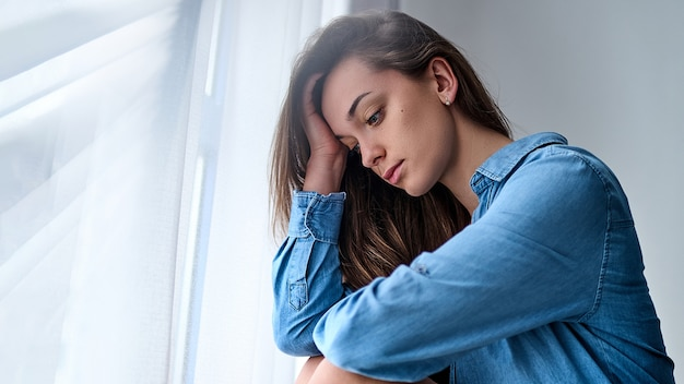 Молодая грустная одинокая задумчивая женщина в рубашке держит голову рукой сидит одна дома у окна во время депрессии и переживаний Premium Фотографии