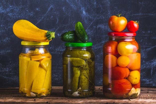Стеклянные банки маринованные домашние, свежие кабачки, огурцы и помидоры на темном фоне. Premium Фотографии