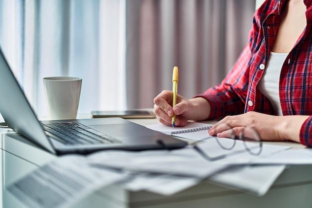 ノートパソコンでオンラインで作業し、ノートにデータ情報を書き留める女性。自宅で遠隔学習中の女性 Premium写真