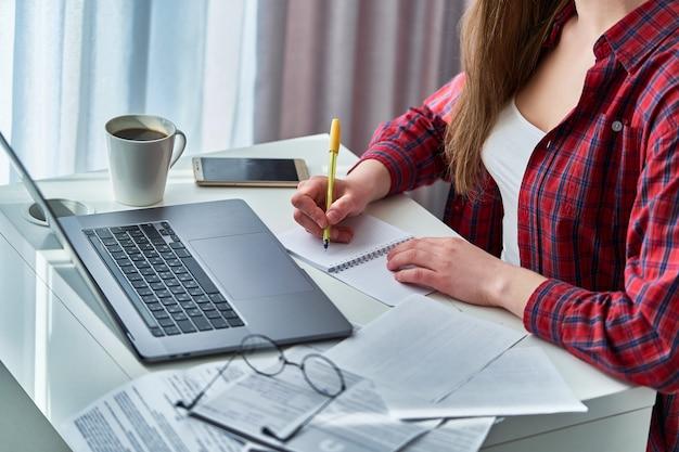 ノートパソコンで作業し、ノートブックの乳製品に重要なデータ情報を書き留める女性ブロガー。自宅で勉強する遠隔教育およびオンラインコース中の女性 Premium写真