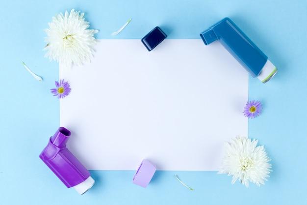 Астма ингаляторы и цветы на синем Premium Фотографии