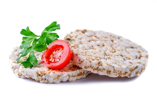 チェリートマトと白い背景の上に新鮮なパセリの孤立した米パン Premium写真