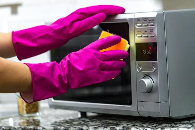 スポンジを使用して電子レンジをクリーニングするゴム手袋の手 Premium写真
