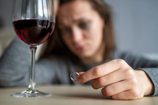 離婚した女性は結婚指輪を手に持って、ワインを飲みます Premium写真