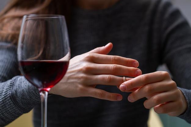 離婚した女性が指から結婚指輪を引っ張り、姦通、裏切り、失敗した結婚のために赤ワインを飲みます。離婚のコンセプト。関係と愛は終わります。人生の問題 Premium写真