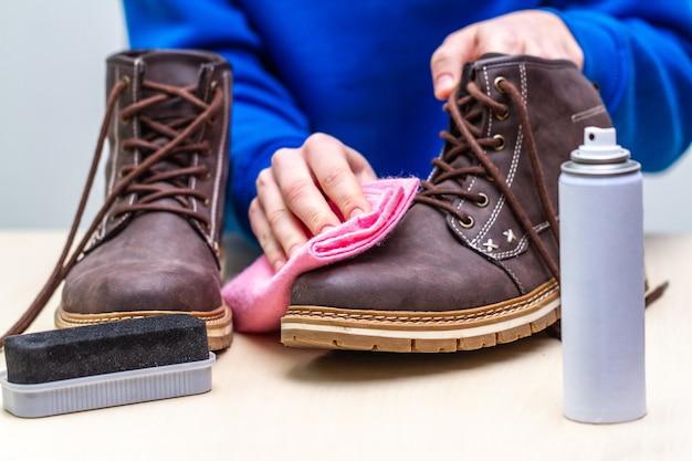 ある人が、男性用のスエードカジュアルブーツをブラシ、ぼろ布、スプレーで掃除しています。靴磨き。履物の水分と汚れの保護 Premium写真