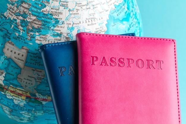 パスポートと青色の背景に地球。旅行、休暇、レクリエーションの。休日、観光、旅行者。 Premium写真