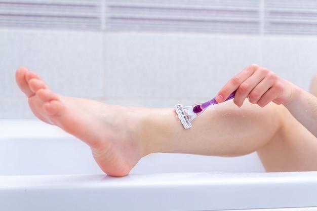 Женщина брить ноги в ванной комнате с помощью бритвы крупным планом. косметические процедуры в домашних условиях Premium Фотографии