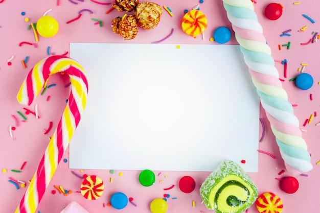 異なる、砂糖、子供のお菓子の背景上のテキストのフレーム。ピンクの背景のお菓子。 Premium写真