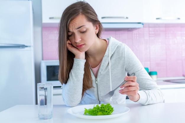 Грустная несчастная молодая женщина устала от диеты и не хочет есть органическую, чистую здоровую пищу Premium Фотографии