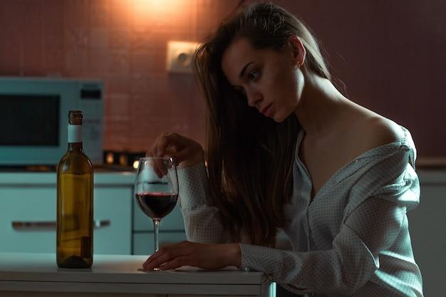 アルコール飲料とブラウスで孤独な悲しい美しい若い女性は、夜自宅で一人で飲んでいます。女性のアルコール依存症とアルコール中毒 Premium写真