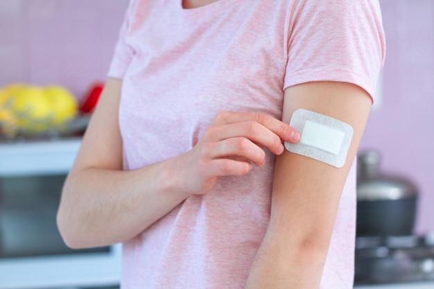 予防接種、注射ワクチンまたは薬の後の腕に医療殺菌粘着包帯を使用して女性。切り傷の応急処置 Premium写真
