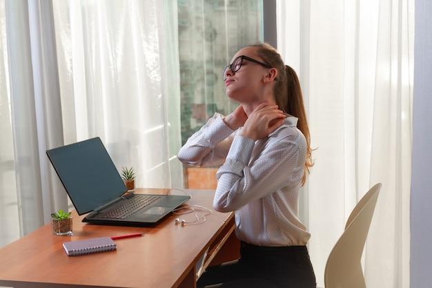 Предприниматель в очках испытывает боли в мышцах шеи и массирует место дискомфорта. сидячая работа. нужен отдых Premium Фотографии