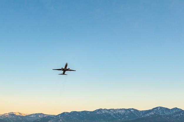 青い空と山の上の飛行機 Premium写真