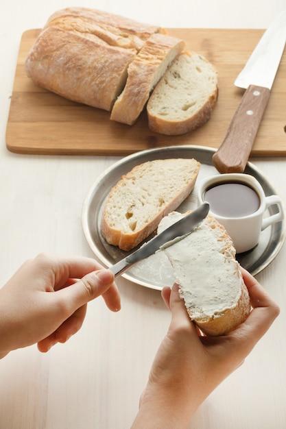 Человек намазывает на хлеб мягкие творожки Premium Фотографии