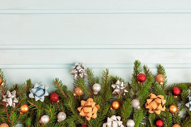 Рожденственский орнамент еловые ветки украшены разноцветными шариками и декоративными бантиками. Premium Фотографии