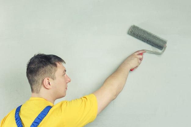 家の画家が壁を処理します。ローラーを保持している修理工。に対して作業服の男。 Premium写真
