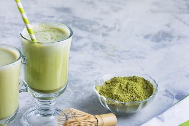 健康的な食事のラテ。抹茶緑茶ドリンクを飲みながらガラスをクローズアップ。テキスト用のスペース。 Premium写真